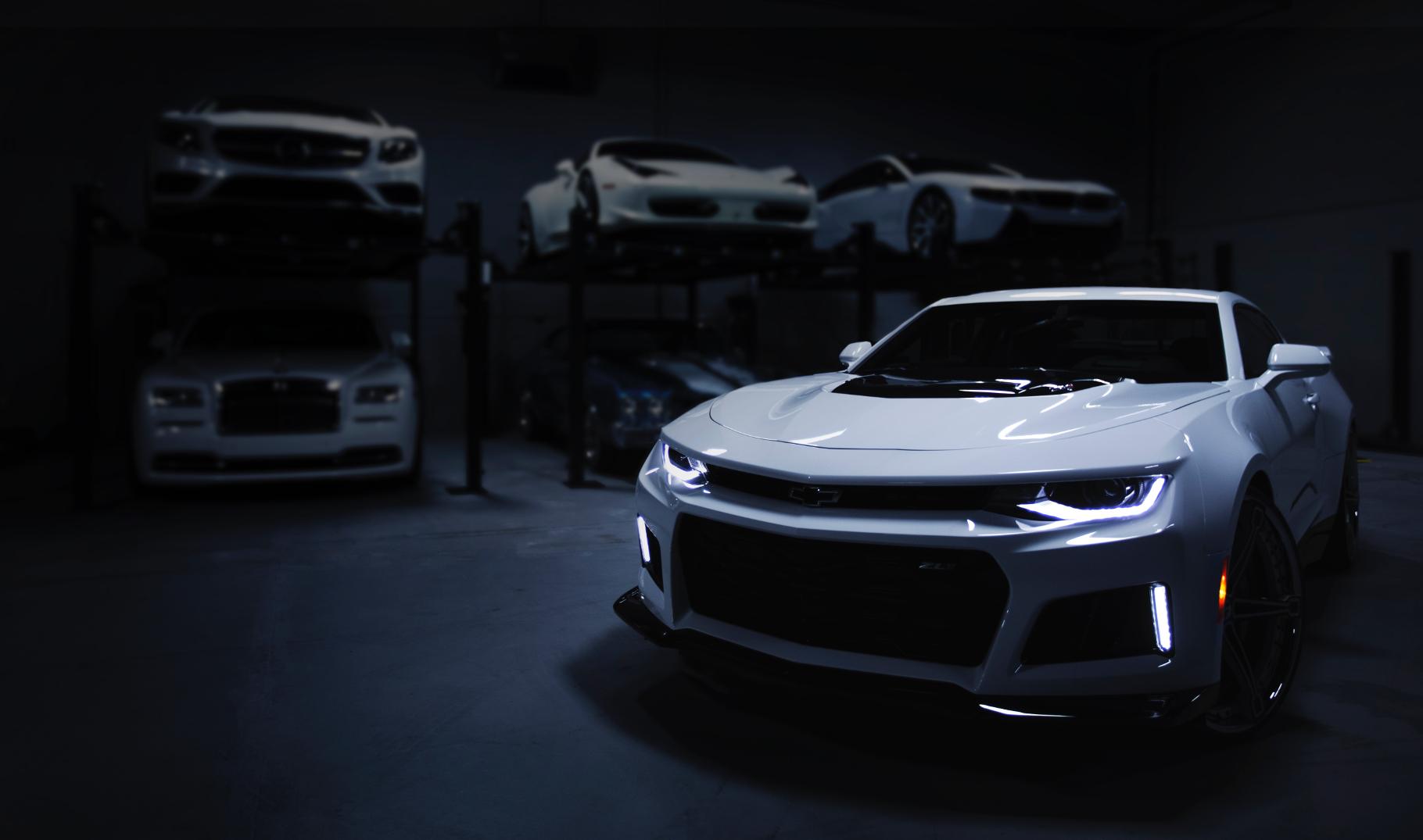 Ein weißes Sportauto steht vor einem dunklen Hintergrund