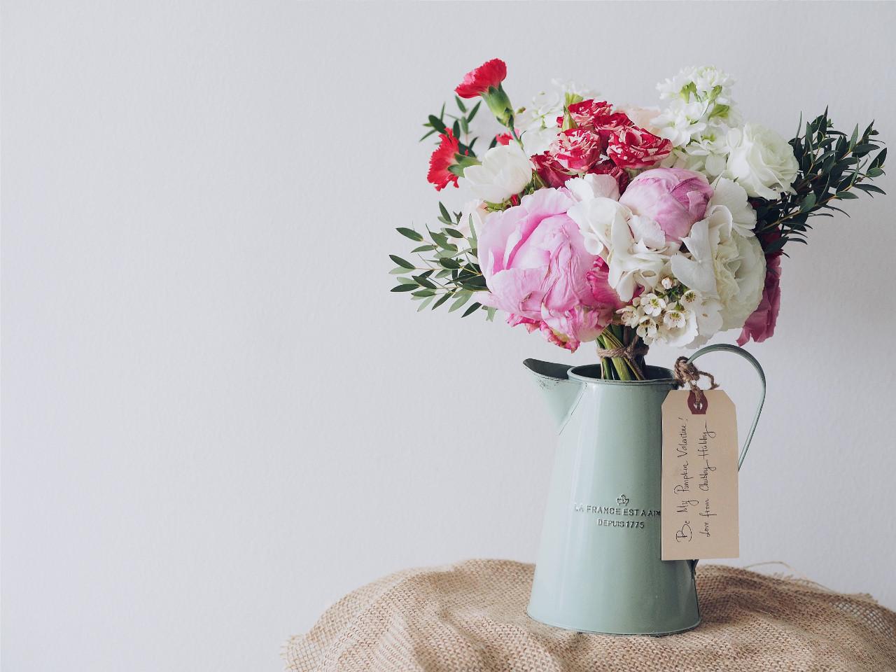 In einer Metallkanne steht ein Strauß mit vielen hellen Blumen. Am Rand hängt eine Grußkarte